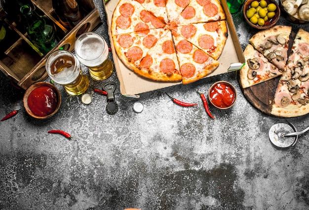Tło pizza. pepperoni z piwem na rustykalnym stole.