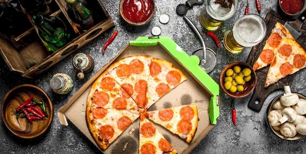 Tło pizza. pepperoni z piwem. na rustykalnym tle.