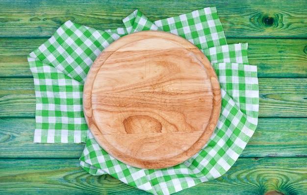 Tło pizzy. okrągła deska do krojenia na zielone obrusy w kratkę na stole, widok z góry