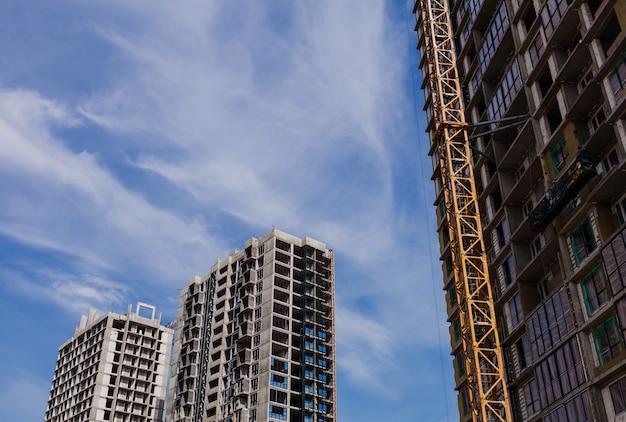 Tło placu budowy. dźwigi i nowe wielopiętrowe budynki na tle nieba