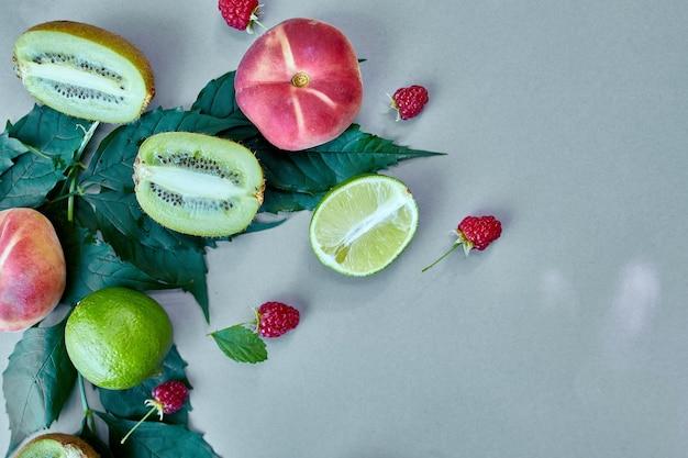 Tło płaskie leżał owoce brzoskwinia, kiwi, malina, limonka na szarym papierze, modny cień i światło słoneczne, słońce, minimalna koncepcja lato, miejsce.