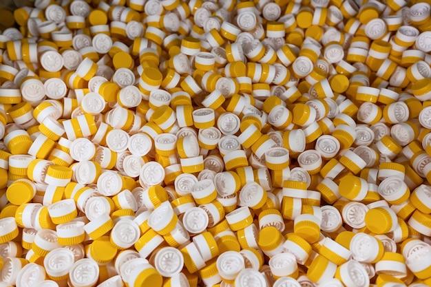 Tło plastikowych kapsli plastikowych kapsli do butelek żółtego i białego