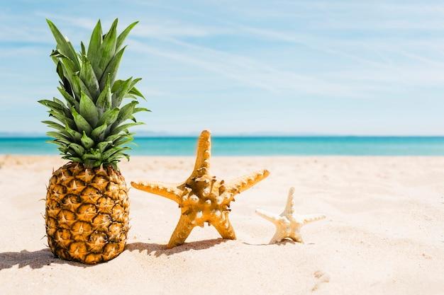 Tło plaża z ananasem i rozgwiazdy