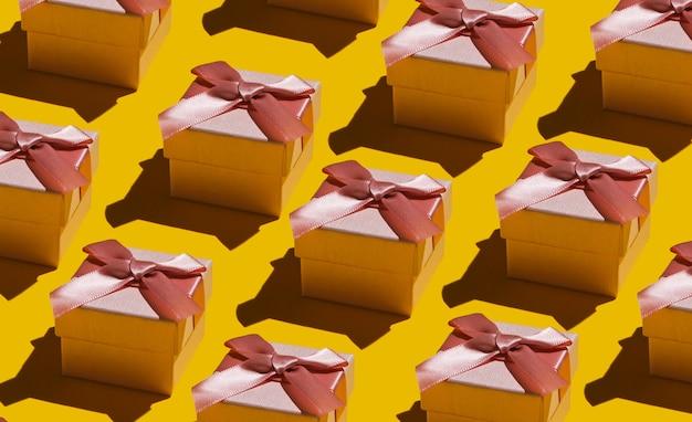 Tło pop-artu. wiele pudełek z kokardą na żółtym tle. koncepcja wakacje, urodziny. moda strzał z cienia