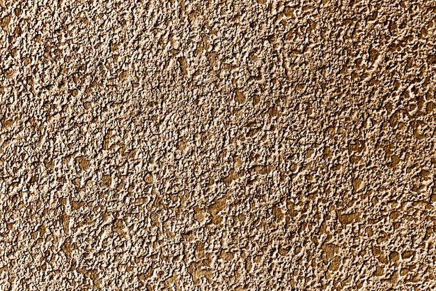 Tło powierzchni ściany betonowej pomalowanej na złoto