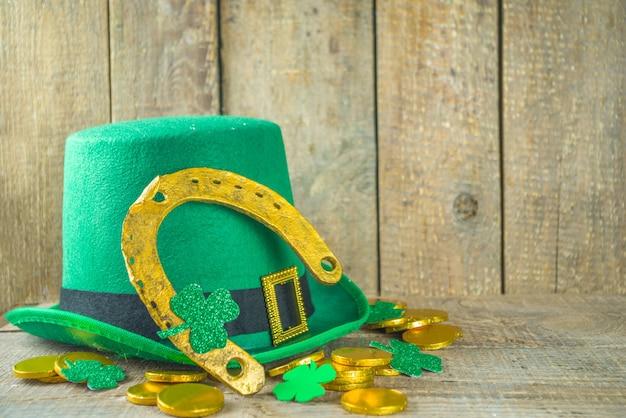 Tło powitania świętego patryka. patryka, szablon zaproszeń, menu. z symbolami świątecznymi - złota podkowa, zielona koniczyna, czapka krasnala, złote monety,