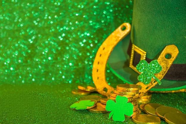 Tło powitania świętego patryka. patryka, szablon zaproszeń, menu. z symbolami świątecznymi - złota podkowa, zielona koniczyna, kapelusz krasnala, złota moneta