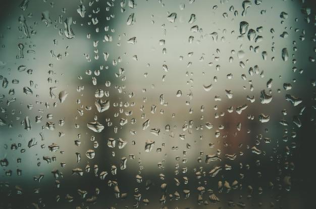 Tło przez deszczową kroplę i krople wody na szybę.