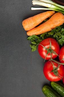Tło puste czarny kolor ze świeżych zdrowych warzyw - zielona cebula, ogórek, pomidory marchew i pietruszka. widok z góry.