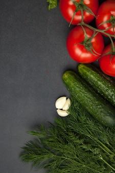 Tło pusty czarny kolor ze świeżych zdrowych warzyw, zielonej cebuli, ogórka, pomidorów. widok z góry.