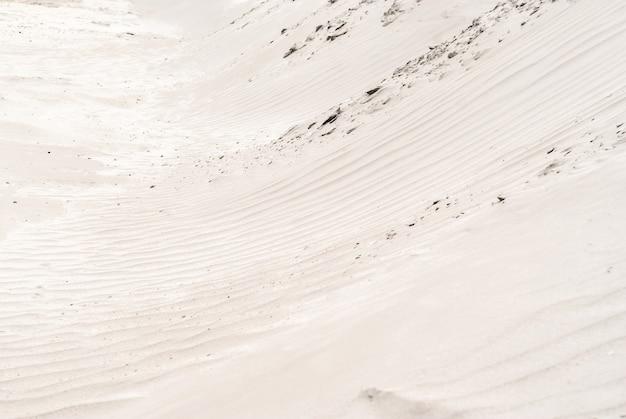 Tło - pustynne wydmy z bliska, zmarszczki na powierzchni piasku