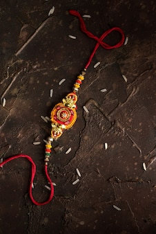 Tło raksha bandhan z eleganckim rakhi i posypanym ryżem