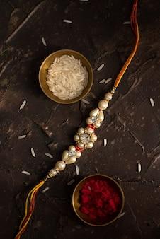 Tło raksha bandhan z eleganckim rakhi, ziarnami ryżu i kumkum