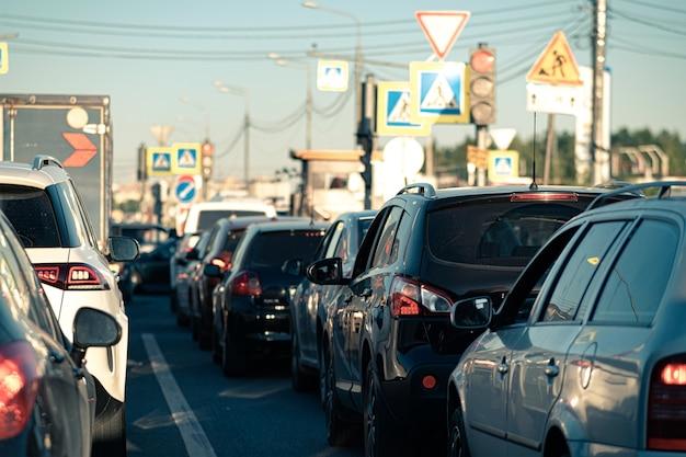 Tło, rozmycie, nieostre, bokeh. korki w godzinach szczytu po pracy. czerwone światła hamowania zatrzymanych samochodów na tle dzielnicy miasta.
