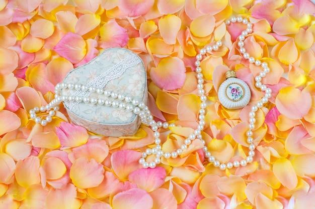 Tło różowe płatki róż, pudełko z biżuterią, perłowe koraliki i butelka perfum
