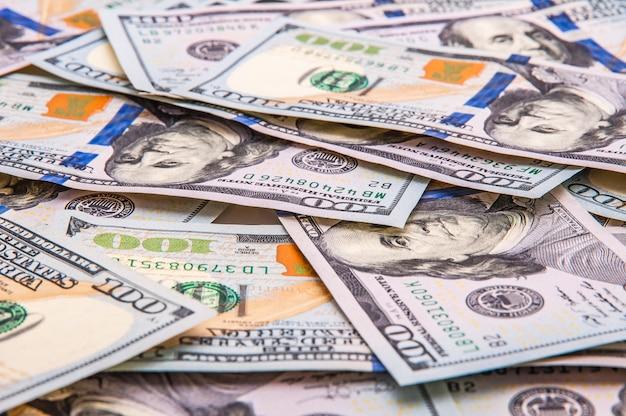 Tło rozrzuconych sto dolarów banknotów.