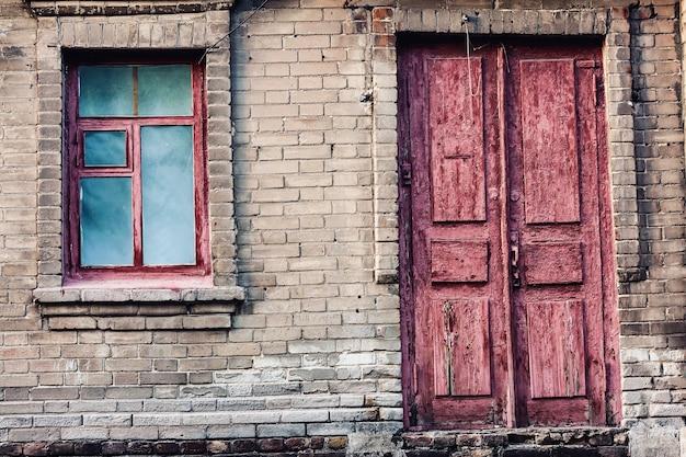 Tło ściany starego opuszczonego domu z drzwiami i oknem.