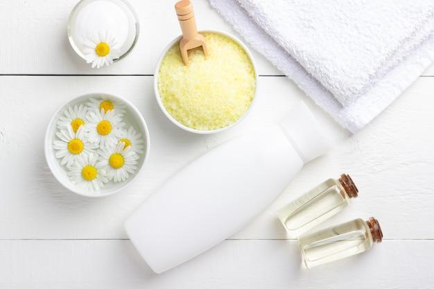 Tło spa z kąpieli żółta sól morska, naturalny krem i rumianek na białym drewnianym stole