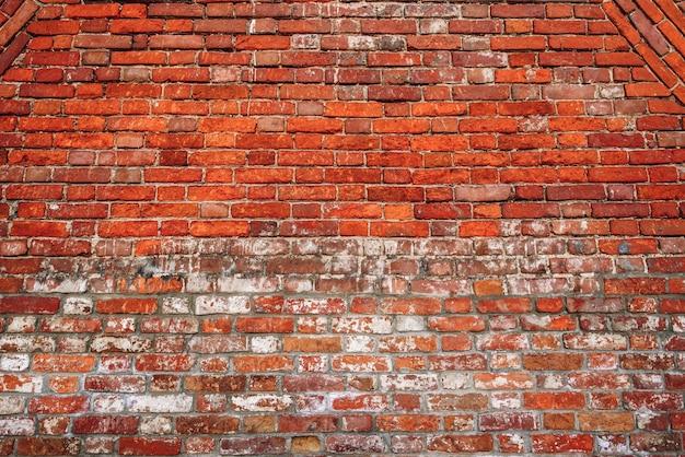 Tło starego rozdrobnionego muru z czerwonej cegły.
