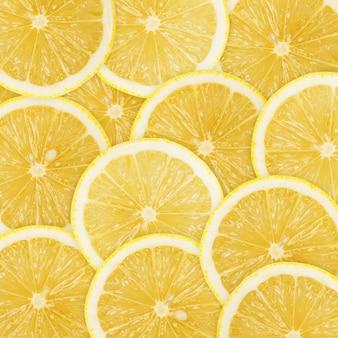 Tło sterty świeżych plasterków cytryny żółty