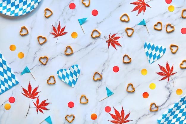 Tło strony oktoberfest. mieszkanie leżało na marmurowym stole. bawarskie, niebiesko-białe, jednorazowe papierowe talerze i papierowe flagi.