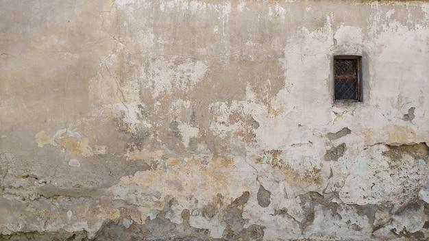 Tło. strych. gips. stare malowane ściany z oknem. zabytkowa tekstura elewacji