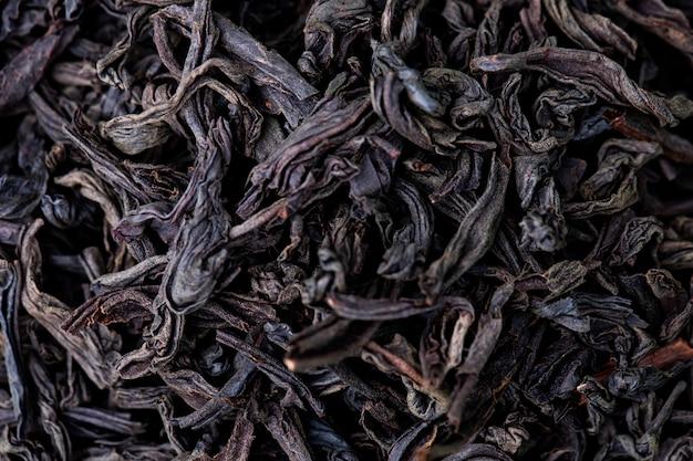 Tło sucha czarna herbata opuszcza teksturę, odgórny widok