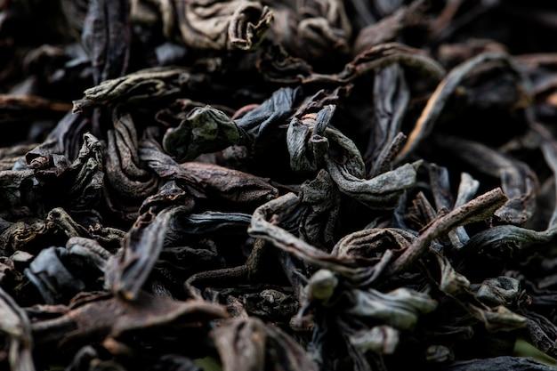 Tło sucha czarna herbata opuszcza teksturę