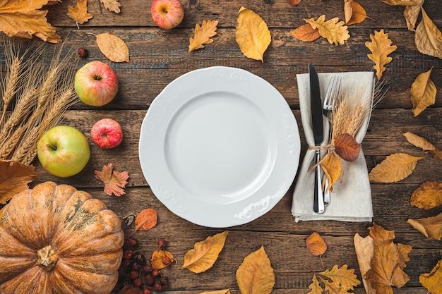 Tło święta dziękczynienia z jabłkami z dyni sztućców i suchymi liśćmi