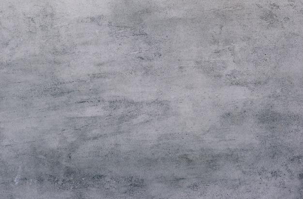 Tło szarej, powleczonej stiukiem i pomalowanej powierzchni, szorstka odlew z cementu i betonowej ściany