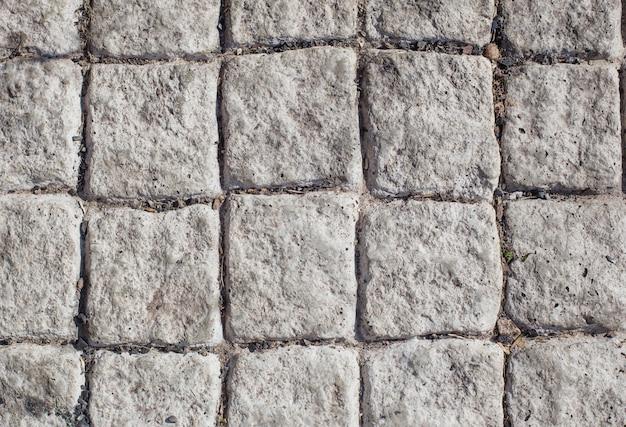 Tło szarych kamiennych płyt chodnikowych w słońcu