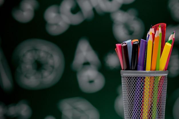 Tło szkoły z akcesoriami papeterii. książki, kula ziemska, ołówki i różne artykuły biurowe leżące na biurku na zielonym tle tablicy