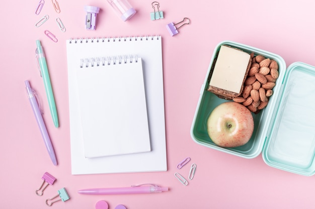 Tło szkoły z notebookami i pastelowe kolorowe akcesoria badania na różowym tle lunch box z jabłkiem, kanapki