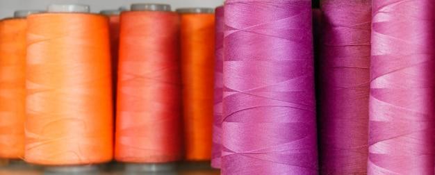 Tło - szpulki z czerwonymi i fioletowymi nitkami zbliżenie