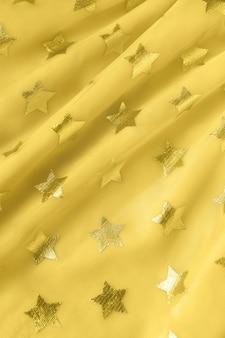 Tło, tekstura jasnożółtej tkaniny siatkowej z gwiazdami. koncepcja modny kolor roku 2021 rozświetlająca, odświętna odzież kobieca, świąteczna, urodzinowa. do mediów społecznościowych, bloga, książki. skopiuj miejsce.