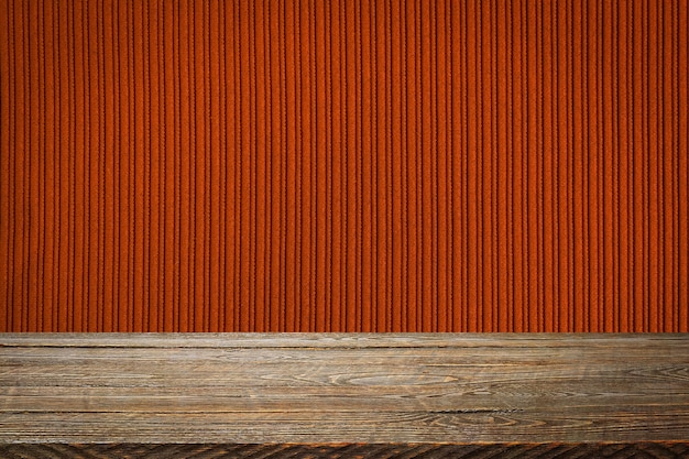 Tło to puste drewniane deski i teksturowana ściana w paski z gradientowym oświetleniem