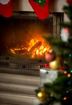 Tło udekorowanej choinki przed płonącym kominkiem w domu