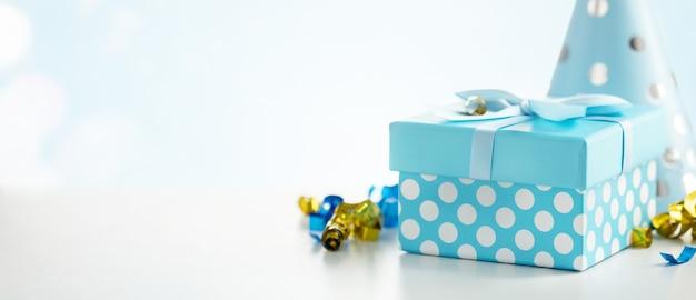 Tło uroczystości z pudełkiem prezentowym, kolorowymi serpentynami, konfetti i czapkami urodzinowymi