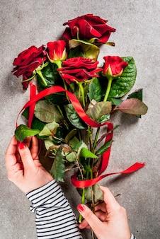Tło uroczysty, walentynki. dziewczyna (ręce na zdjęciu) robi bukiet czerwonych róż, zawiązuje czerwoną wstążką