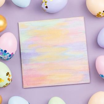 Tło uroczysty wesołych świąt z zdobione jajka, kwiaty, słodycze i wstążki w pastelowych kolorach na białym tle. skopiuj miejsce