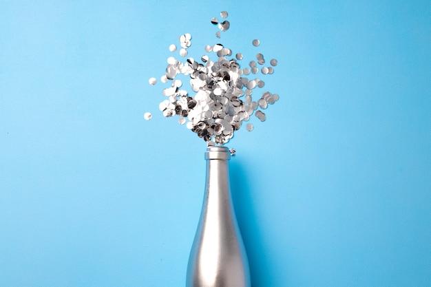 Tło uroczysty z butelką szampana i konfetti