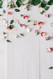 Tło valentine, różowe kwiaty róży i płatki rozrzucone na białym rustykalnym drewnie, widok z góry z miejscem na kopię. makieta szczęśliwy dzień kochanków