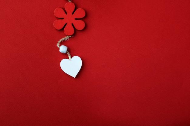 Tło valentine's day. białe serce pod czerwonym kwiatem na czerwonym tle.