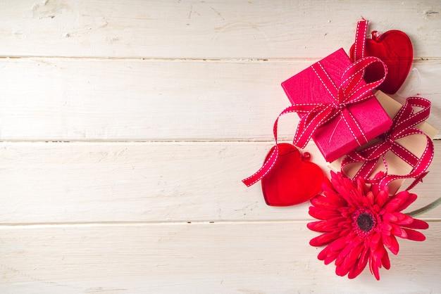 Tło valentine's day. pudełka na prezenty z świąteczną wstążką, szklanym czerwonym sercem i czerwonym kwiatem gerbera na jasnym drewnianym tle. skopiuj miejsce na tekst