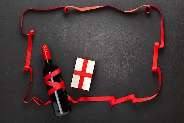 Tło valentine's day. wino i dwie szklanki, prezent i pusta kartka na życzenie, prezent i czerwone serduszka na czarnym tle.