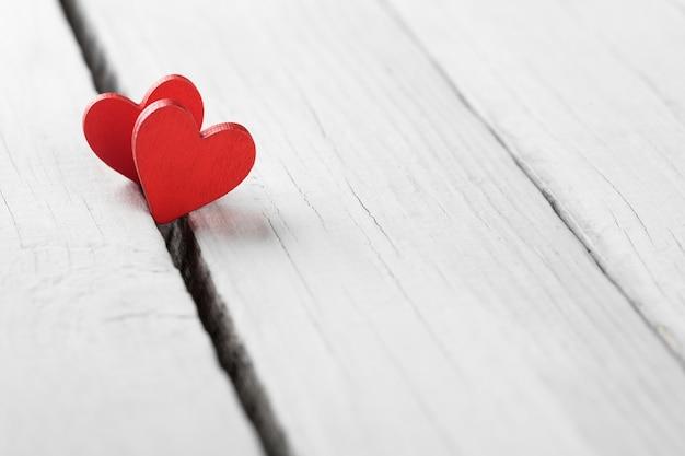 Tło valentine z ręcznie robionymi sercami na rustykalnym drewnie