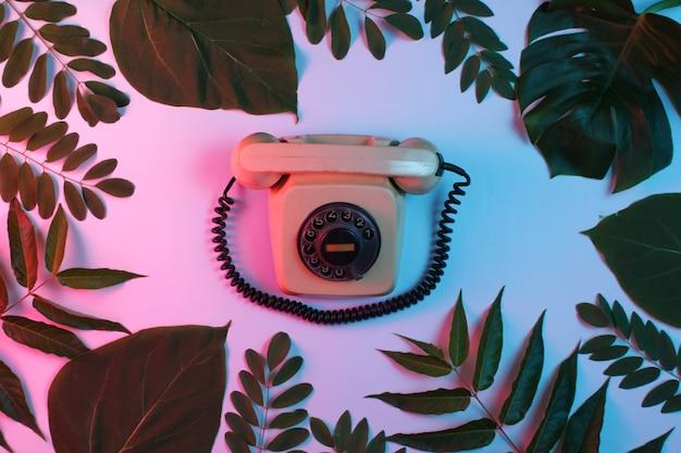 Tło w stylu retro. retro obrotowy telefon wśród zielonych liści na tle z gradientowym neonowym niebieskim różowym światłem.