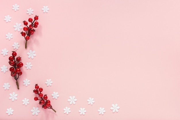 Tło wakacje, gałązki głogu na różowym tle z płatkami śniegu, leżał płasko, widok z góry