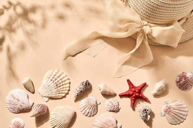 Tło wakacje letnie. imitacja piasku plażowego z muszlą, rozgwiazdą i damskim kapeluszem