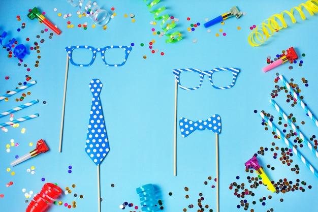 Tło wakacje lub party ze słomkami, gwizdkami, konfetti, zabawnymi okularami i chorągiewką